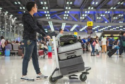 Young asian man holding cart of suitcase or baggage with airport luggage trolley in the international airport.