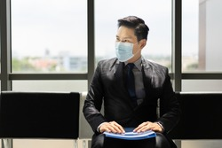 Young Asian man in a black tie, suit, and trousers wearing a face mask for protective covid-19 sitting on a chair with a blue folder on his lap waiting for a job interview at the office reception area