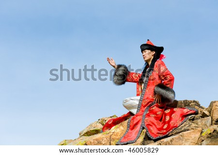 young asian man in fine Mongolian suit sits on rock stretching out his arm forward, in profile, his name Chinghis is painted in ancient Mongolian on his face