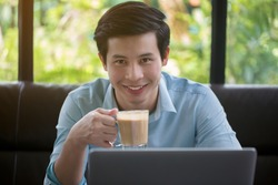 Young Asian man is drinking coffee in cafe