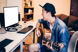 Young Asian man learning how to play guitar on computer monitor. Male guitarist watching online tutorial. Include clipping path on monitor