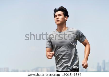 young asian man male runner jogger running jogging outdoors ストックフォト ©