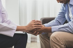 Young asian man, male suffers from a mental who needs to therapy with a psychologist while sitting on couch to consult, psychiatrist has encouragement the patient by touching to make his feel relaxed.