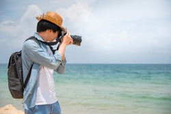 Young Asian man photographer and traveler holding digital camera taking photo of tropical island beach and sea. Travel photography on summer holiday vacation. Relaxation and carefree concepts
