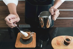 young asian man pouring milk froth into the cappuccino cup. barista and coffee cafe concept