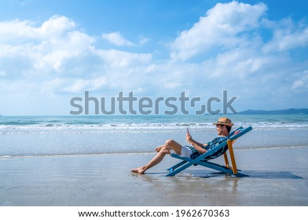 Young Asian man resting on sunbed on tropical beach. Happy guy sit on beach chair by the sea using smartphone for selfie or video call. Handsome male enjoy beach outdoor lifestyle on summer vacation