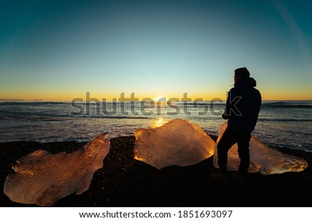 Young Asian man standing on black volcanic sand beach among big diamond-shaped ice rocks at Diamond Beach, Iceland, admire beautiful seascapes and calm blue sky at sunrise or sunset in front of him. Photo stock ©