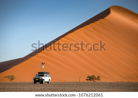 Young Asian man traveler and photographer standing on camper car near orange sand dune. Travel desert concept