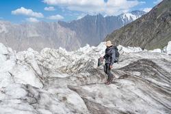 Young Asian man trekker with backpack walking on Passu glacier in Patundas trekking route in Karakoram mountains range, Hunza valley, North Pakistan, Asia