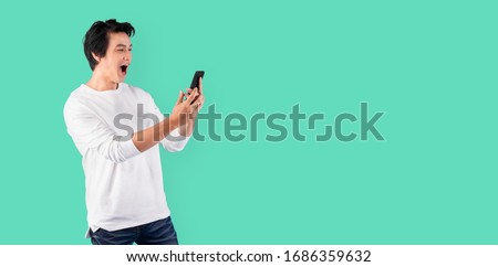 Young Asian man using mobile phone with happy and cheerful over green background with copy space