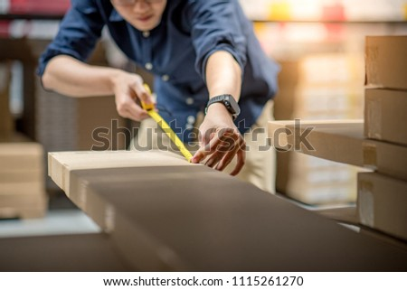 Young Asian man using tape measure for measuring dimension of product in cardboard box. Shopping lifestyle in warehouse concept ストックフォト ©
