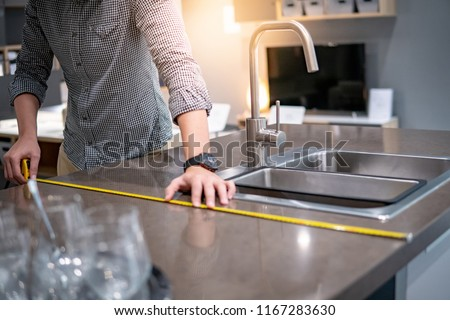 Young Asian man using tape measure for measuring granite countertops on modern kitchen counter in showroom. Shopping furniture for home improvement. Interior design concept