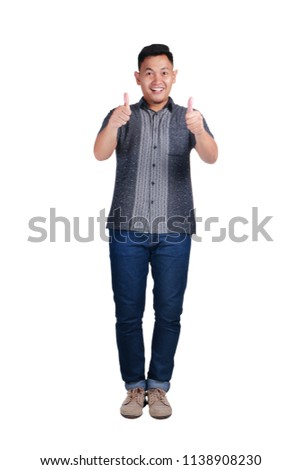 Young Asian man wearing blue jeans and batik shirt, proud and thumbs up gesture. Isolated on white. Full body portrait