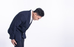 Young asian man wearing formal suit and bowing to pay respect or be sorry while standing on white background with copy space. Business Manner Concept.