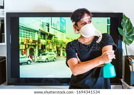 Young asian man with funny created mask from brassiere is imitating sanitizing near TV screen. Stay at home isolation. Alternative face mask for protecting from virus. Fighting against coronavirus