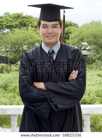 Young Asian man with graduation cap and gown