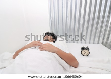 Young Asian man with mask comfortable sleeping on the bed in home. #1066480604
