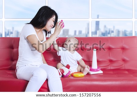 Young asian mother and baby playing toys at home
