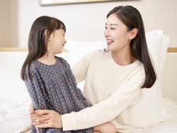 young asian mother and elementary age daughter sitting in bed relaxing playing chatting at home