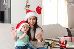 Young Asian mother and her little son staying at home on Christmas holidays making video call and waving hand to family or friends. New normal life lockdown during coronavirus,COVID-19 pandemic.