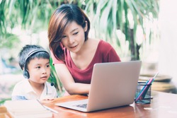Young asian mother and son using laptop computer for study and learning together at home, boy wearing headphone for e-learning with distancing, teacher or mom support child, education concept.