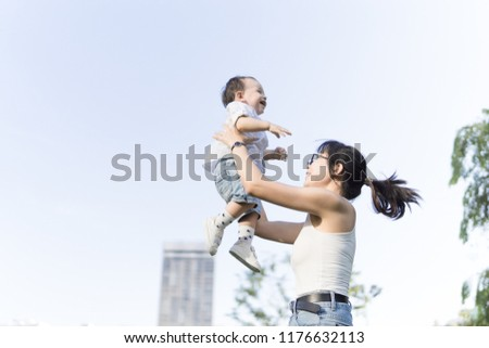 Young Asian mother holding and playing launching his happy baby boy in the air while he similes and laughs outdoors #1176632113