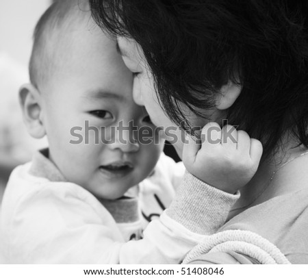 young asian mother holding her 2-year old son with eyes closed; black and white.