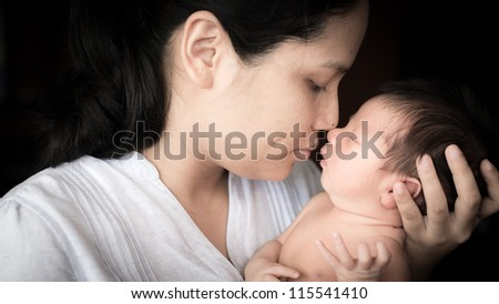 Young Asian mother lovingly holds her newborn baby boy (5 days old)
