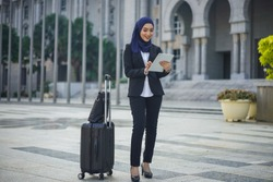 Young Asian Muslim corporate waiting with suitcase while holding tablet
