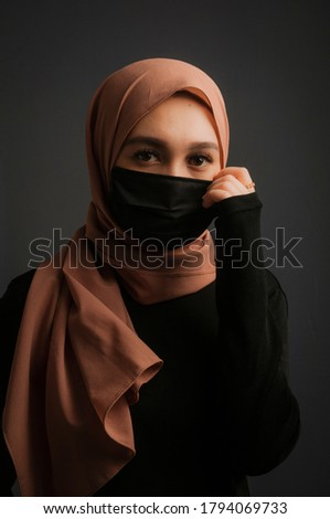 Young Asian Muslim woman wearing face shield or clothes mask in modern fashion lifestyle as health protocol in new normal era while doing activities Stok fotoğraf ©