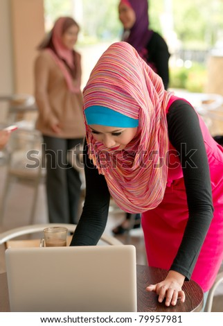 Young Asian Muslim women talking each others at coffee shop