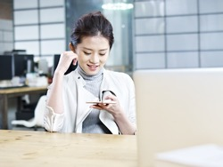 young asian office woman looking at cellphone and smiling.