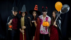 Young Asian People in Costumes Celebrating Halloween.Group of Young Happy Friends Wearing Halloween Costumes witch having Fun at Party in Nightclub by doing Scary faces. Celebration of Halloween party