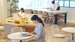 Young asian people working in the office. Co-working space. Social distancing.