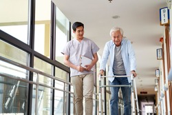 young asian physical therapist working with senior man on walking using a walker