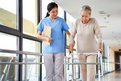 young asian physical therapist working with senior woman on walking with a walker