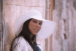 Young asian pregnant woman in white hat near old building