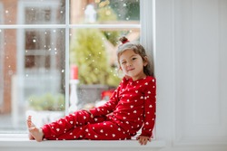 Young asian pretty girl in pyjamas in red hearts posing on the big window with snow background. High quality photo