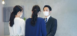 Young asian receptionist talking with customers with surgical mask. Hotel worker. Store clerk.