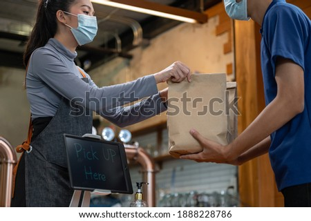 Young Asian restaurant owner or waitress wearing face mask giving takeaway food bag to delivery man. Male courier taking online order for delivery at restaurant. Takeaway food during covid-19 pandemic
