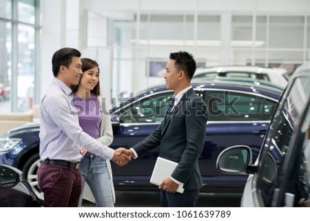 Young Asian salesman greeting couple in car dealership #1061639789