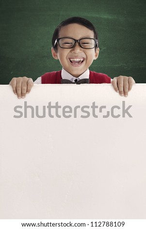 Young asian schoolboy showing blank copy space. shot in the class