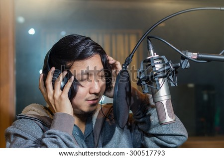 Young Asian singer recording a song with microphone in music studio