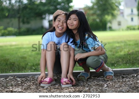young asian sisters hugging