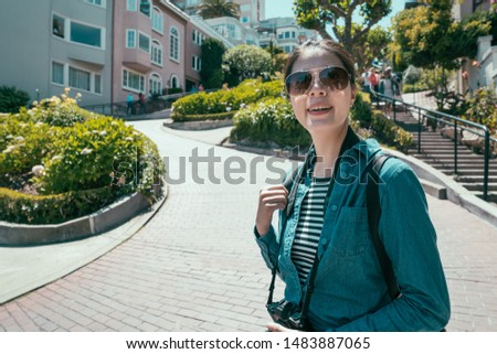 young asian smiling lady traveler standing on Lombard street on Russian hill San Francisco. happy tourist woman in sunglasses relax under sunshine in famous attraction beautiful green spring garden #1483887065