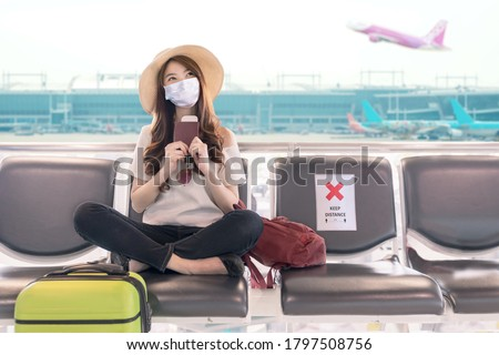 Young asian student college girl sitting at airport terminal wear medical mask feeling happy with safety travel bubble plan after covid pandemic and waiting for flight in fit to fly in asia concept.