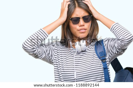 94617345027 Hands on head. Young asian student woman wearing headphones and backpack over  isolated background suffering from headache desperate and
