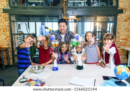 Young Asian teacher doing experiments with dry ice for children at classroom in modern school. During experiment scientist holds flask showing reaction smoke and colored liquid.