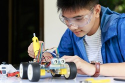 Young asian teen plugging energy and signal cable to sensor chip of toy car workshop.