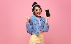 Young Asian teen woman showing smart phone she listening music in headphones isolated on pink background.